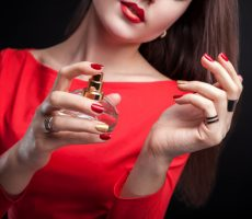woman-applying-perfume-her-wrist-black-background_106029-78