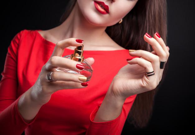woman-applying-perfume-her-wrist-black-background_106029-78